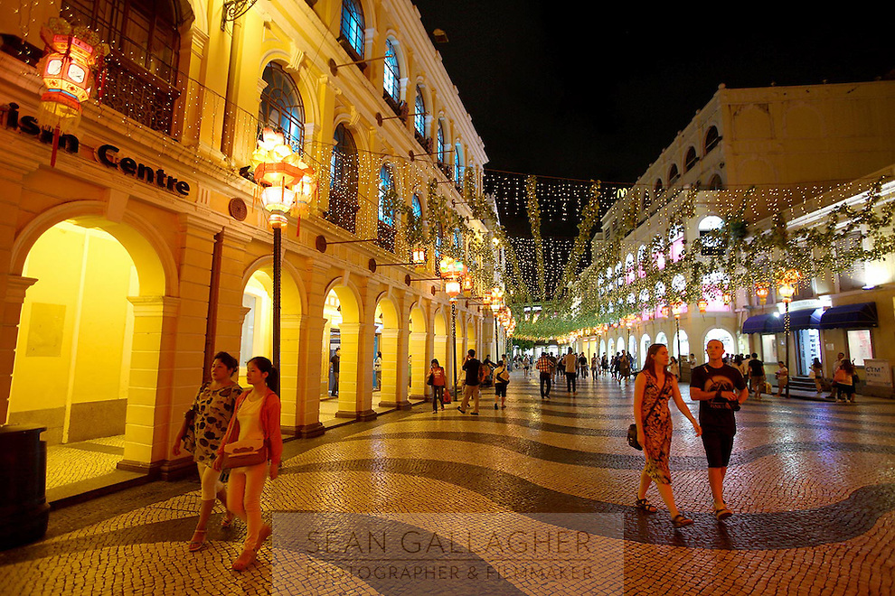 People walking through colorful Senado Square at night.<br />