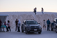 People gather in the parking area near the curved picnic shelters as the sun sets at White Sands National Monument near Alamogordo, New Mexico, USA, on Sat., Dec. 30, 2017.