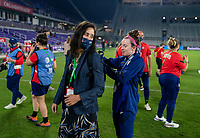 ORLANDO, FL - FEBRUARY 24: Kate Markgraf stands as Rose Lavelle #16 of the USWNT puts her MVP trophy in a backpack during a game between Argentina and USWNT at Exploria Stadium on February 24, 2021 in Orlando, Florida.