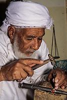 Rustaq, Oman.  Rashid al-Obeidani, Silversmith, in his Workshop, Hammering a Design into a Ring.