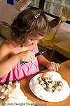 Preschool ages 3-5 girl using magnifying glass to look at shells and bird eggs vertical nature study