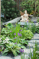 Asian Oriental statue ornament in garden with irises, candlestick primroses, pine tree, stone path walkway, in spring blooms, around a water feature