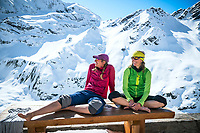 Women sitting on the deck of the Turtmann Hut during a spring ski tour in the Swiss Alps.