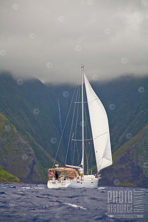 Cruising yacht sailing downwind along the vertical sea cliffs of Molokai, Hawaii