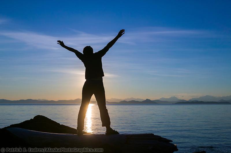 Lady celebrates nature as the sun sets over the Kenai mountains and the Chugach National Forest, Eleanor Island, Prince William Sound, Alaska