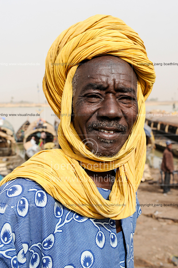 MALI, Mopti, river Niger, port with pinnace boats, market day, man with headgear, a coloured cloth called shesh or Tagelmust, the turban of Touareg, Haussa and Songhai / Mali, Mopti, Fluss Niger, Markttag und Warenhandel im Hafen mit Pinassen