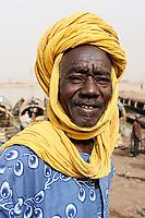 MALI, Mopti, river Niger, port with pinnace boats, market day, man with headgear, a coloured cloth called shesh or Tagelmust, the turban of Touareg, Haussa and Songhai / Mali, Mopti, Fluss Niger, Markttag und Warenhandel im Hafen mit Pinassen
