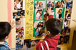 Educaton preschool  3-4 year olds separation two boys in dressup clothes looking at wall display of photos of parents and children one boy reaching up to touch photo of his mother holding him horizontal