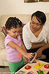 Toddler girl, age 2, at home with mother, playing with geometric shapes, mother talking and encouraging