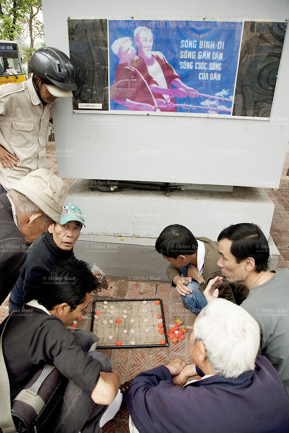 Vietnam. Hanoi. A group of men, kneeling play a board game on the street. Poster celebrating the communist victory with the figure of Ho Chí Minh (May 19, 1890 - September 2, 1969) who was a Vietnamese Communist revolutionary and statesman as Prime Minister (1946-1955) and President (1946-1969) of the Democratic Republic of Vietnam (North Vietnam). Ho Chí Minh led the Viet Minh independence movement from 1941 onward, establishing the communist-governed Democratic Republic of Vietnam in 1945 and defeating the French Union in 1954. He lost political power inside North Vietnam in the late 1950s, but remained as the highly visible figurehead president until his death. Red flag of the Vietnamese Communist Party.  04.04.09 © 2009 Didier Ruef