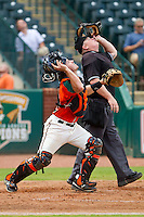 Greensboro Grasshoppers catcher Tony Caldwell (29) and home plate umpire Kevin Morgan both rip off their masks as they track a pop fly during the South Atlantic League game against the Augusta GreenJackets at NewBridge Bank Park on August 11, 2013 in Greensboro, North Carolina.  The GreenJackets defeated the Grasshoppers 6-5 in game one of a double-header.  (Brian Westerholt/Four Seam Images)