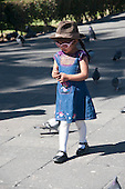 "Arequipa, Peru. Plaza de Armas (public square). Young girl (Peruvian) feeding pigeons. The cloth hat she is wearing is known as ""monteras,"" which are common in South America and vary in style by region. No MR. ID: AL-peru."