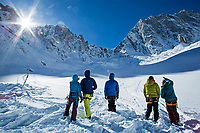 Group of friends warming themselves up with the first rays of sun on the Lechaux Glacier, French Alps