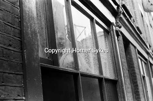 Whitechapel London. 1978<br /> In a road just off Brick Lane, a lone Asian woman stares out of her flat window. There had been reports in the press that many new immigrants to Britain, and in particular Bangladeshi women were being kept under lock and key by their men folk. They didn't speak the language and were rarely allowed out of their homes