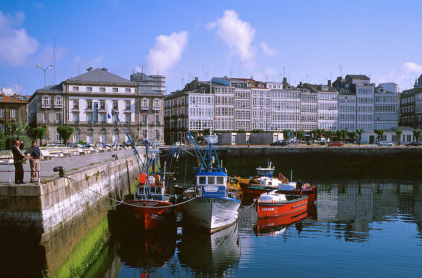 Spain, Galicia, La Coruna. Boats in marina. Houses facing waterfront with glassed in balconies, a typical building style in La Coruna, which lead to it being dubbed city of glass.