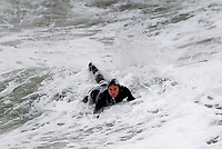 BNPS.co.uk (01202 558833)<br /> Pic: ZacharyCulpin/BNPS<br /> <br /> Pictured: Surfs up - A man waits for a good wave at Bournemouth Pier. <br /> <br /> Strong coastal winds brought huge waves to Bournemouth beach last night. Surfers braved the cold weather and made most of the conditions at Bournemouth Pier.