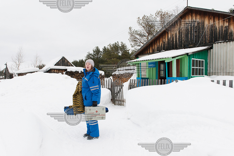 Paramedic Olga standing in front of a small health clinic in a remote community where she has flown in by helicopter to collect a patient and travel with them to hospital.