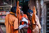 Holy men stop at a shop to buy religious items in the ancient city of Varanasi in Uttar Pradesh, India. Photograph: Sanjit Das/Panos