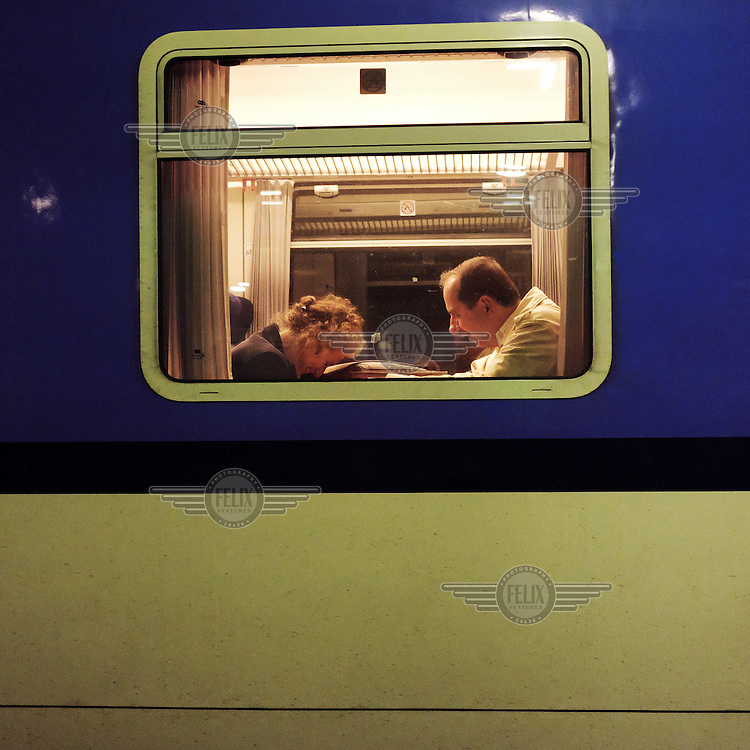 A man and a woman seen through the window of a train at the Prague Main Train Station.