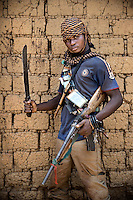An Anti-Balaka (Anti-Machete) fighter holding an AK47 and a machete and draped with 'Gris Gris' amulets that confer good fortune and protection on the wearers. They are animist in origin but also worn by both Muslims and Christians throughout west and central Africa. In late 2012 after years of instability and conflict, the Seleka, a predominantly Muslim rebel group, fuelled by grievances against the government, overran the country and, In March 2013, ousted President Francois Bozize, who fled the country. The rebel's leader Michel Djotodia was proclaimed president in August 2013. He disbanded the Seleka in September 2013 but law and order collapsed and ex-Seleka fighters roamed the country committing atrocities against the civilian population. In an attempt to defend their lives and property vigilante groups, calling themselves Anti-Balaka (Anti-Machete), formed to confront the ex-Seleka fighters but soon began to take reprisals against the wider Muslim population and the conflict became increasingly sectarian. By December 2013, with international fears of a genocide being voiced, French led peacekeepers deployed to the country began to act on a UN mandate to disarm the fighters and protect the civilian population. However, they have struggled to contain the situation. Much of the Muslim population, in particular, have been forced into ghettos where they are suffering from food shortages and limited access to healthcare. Often, only a few peacekeepers stand between them and a massacre by vengeful Anti-Balaka militants. UN reports describe 'thousands' killed, while over 600,000 people have been internally displaced and a further 200,000 have fled the county.