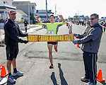 Liam Wall of Manasquan wins first annual Manasquan Turkey Run on Sat., Nov. 22, 2014. Holding the finish line are race director Carmen Triggiano (left) and Manasquan Borough Councilman Owen McCarthy. (Andrew Mills Digital Media)