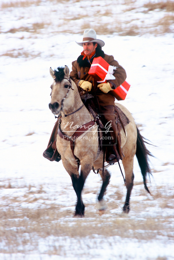 Cowboy on horseback delivering a red Christmas gift box in South Dakota