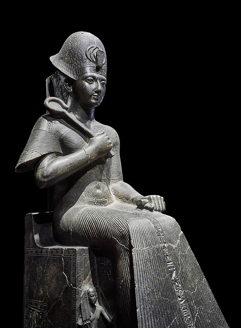 Ancient Egyptian statue of Ramesses II. granodiorite, New Kingdom, 19th Dynasty, (1279-1213 BC), Karnak, Temple of Amon. Egyptian Museum, Turin. Black background.<br /> <br /> Ramesses II is depicted in all his majesty in this ststue. He wears a Khepresh crown and holds the heqa sceptre against his chest. The statue probably belongs to the beginning of Ramesses II reign because of the presence of Queen Nefertari by the throne who died half way through his reign.