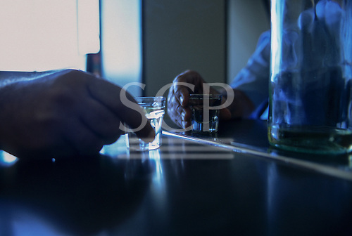 Belgrade, Serbia. Hands on a bar with vodka in shot glasses.