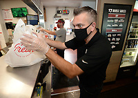 Jason Saragusa, area director for Slim Chickens, prepares a curbside pickup order Thursday, Sept. 10, 2020, while filling orders at the restaurant's location at 5240 W. Sunset Ave. in Springdale. The locally based restaurant continues to expand nationally and has capitalized on its drive-thru and curbside pickup during the pandemic. Visit nwaonline.com/200913Daily/ for today's photo gallery. <br /> (NWA Democrat-Gazette/Andy Shupe)