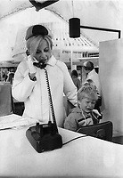1967 FILE PHOTO - ARCHIVES -<br /> <br /> Expo hostess Jane MacKenzie telephones to the fair's lost child centre and asks for an attendant to come and pick up the small and tear-stained lost lad.<br /> <br /> 1967<br /> <br /> PHOTO : Boris Spremo - Toronto Star Archives - AQP