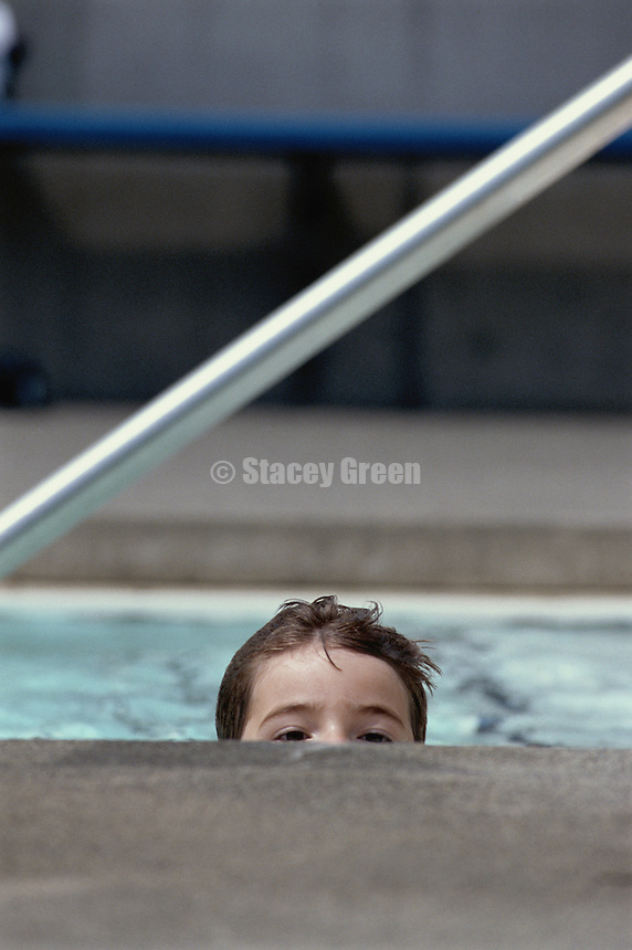 Boy (5-7) looking over edge of swimming pool, high section