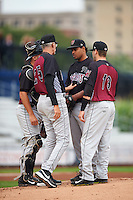 Wisconsin Timber Rattlers pitching coach Gary Lucas (25) talks with pitcher Angel Ventura (38) as catcher Natanael Mejia (14) and first baseman Alan Sharkey (18) listen in during the first game of a doubleheader against the Quad Cities River Bandits on August 19, 2015 at Modern Woodmen Park in Davenport, Iowa.  Quad Cities defeated Wisconsin 3-2.  (Mike Janes/Four Seam Images)