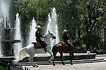 Two Mexican police horsemen ride in the park at Mexico City