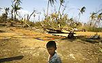 A Cyclone Nargis survivor looks on as he stands next to drying rice in the village of Kamingo, at the Irrawaddy Division, May 10, 2008. Despairing survivors in Myanmar awaited emergency relief on Friday, a week after 100,000 people were feared killed as the cyclone roared across the farms and villages of the low-lying Irrawaddy delta region. The storm is the most devastating one to hit Asia since 1991, when 143,000 people were killed in neighboring Bangladesh. Photo by Eyal Warshavsky  *** Local Caption *** ëì äæëåéåú ùîåøåú ìàéì åøùáñ÷é àéï ìòùåú áúîåðåú ùéîåù ììà àéùåø