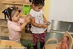 Education Preschool Child care two year old program two toddler girls using cameras to take photos of baby doll