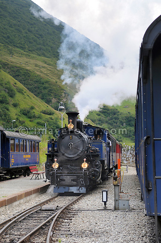 Furka cogwheel railway steam engine DFB 1 arriving at Realp station. Switzerland, Western Europe, Grimsel-/Furka region, Uri. The steam engine HG 3/4 No. 1 Furkahorn DFB 1 was built in 1913. With an engine power of 600 hp and a weight of 42 tons it manages a maximum speed of 45 km/h on adhesion rails and 20 km/h on cogwheel rails. Note: No releases available. --- Info: In 1914 the first steam trains started from Brig and reached Gletsch traveling along the river Rhone. In the following years the line was extended and finally connected in Disentis with the Rhätische Bahn in 1926. Although the Furka-Oberalp-Bahn was electrified in 1942, due to the extreme climate and the topography of this alpine area the trains could not run between Oberwald and Realp through the winter. So in the 1970's a modern tunnel was built for all year use. In 1983 the Furka Cogwheel Steam Railway Club was founded by railway enthusiasts to repair and maintain the original track and rolling stock. This included bringing back and restoring the original steam engines that were sold of to Vietnam in 1947. In late summer 2010 the historic steam link over the Furkapass was finally fully reestablished!