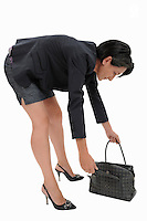 Businesswoman looking inside her handbag (Licence this image exclusively with Getty: http://www.gettyimages.com/detail/103933319 )