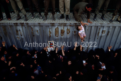 """Tehran, Iran .June 9, 1989..Hundreds of thousands of mourners visit the grave site for the Grand Ayatullah Sayid Ruhullah Musawi Khomeini in the Beheht-E-Zahra cemetery. Mothers have soldiers on top of the tomb, touch their baby's to the grave walls as a blessing. He died of heart attack on June 3, 1989...Khomeini was a senior Shi`i Muslim cleric, Islamic philosopher and marja (religious authority), and the political leader of the 1979 Iranian Revolution that saw the overthrow of Mohammad Reza Pahlavi, the last Shah of Iran. Following the revolution, Khomeini became the country's Supreme Leader?the paramount political figure of the new Islamic Republic...Khomeini was a marja al-taqlid, (source of imitation) and important spiritual leader to many Shia Muslims. He was also an innovative Islamic political theorist, most noted for his development of the theory of velayat-e faqih, the """"guardianship of the jurisconsult (clerical authority)"""". He was named Time's Man of the Year in 1979 and also one of Time magazine's 100 most influential people of the 20th century."""