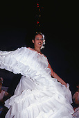 Foz do Iguassu, Brazil. Folklore; girl in white swirling traditional dress dancing.