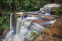 Giluk Falls plunge over the edge of the southern plateau of the Maliau Basin into dense lowland dipterocarp rainforest. Alternating layers of soft, easily-eroded mudstone and harder sandstone have given rise to a series of exposed sandstone shelves over which the falls cascade. Center of the Maliau Basin, Sabah's 'Lost World, Borneo, Malaysia.