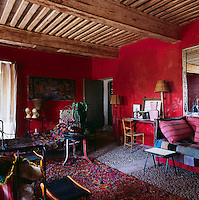 A bold red living room with a low beamed ceiling. The room is a riot of vibrant colour and pattern. Iron campaign beds provide seating and are covered with floral patterned wool blankets. The older furniture contrasts with plastic-topped 1950s tables. A desk and chair arrangement stands against one wall.