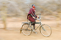 Maasai man cycling, Tipilit Village, near Amboseli National Park, Kenya