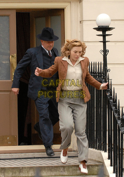 """*EXCLUSIVE*.MICHAEL KITCHEN & HONEYSUCKLE WEEKS.Filming the three part ITV Series """"Foyle's Peace"""" a spin-off of the hit tv show """"Foyle's War"""" at a location in Bloomsbury, London, England, .April 9th 2009..film Tv set filmset costume filming scene Full length brown jacket cream shirt blouse grey gray trousers brown jacket running funny .CAP/IA.©Ian Allis/Capital Pictures"""