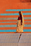 A woman walks along the Varanasi ghats, or steps down to the holy Ganges River, past sheets spread out to dry.
