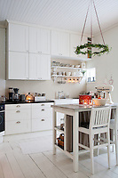 A simple IKEA kitchen and island have been spruced up with a custom made concrete worktop, stainless steel handles and a delicately patterned wallpaper
