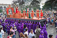 Antigua, Guatemala.  Spectators, Family, and Tourists Watch Adolescent Boys Carrying a Float in a Religious Procession during Holy Week, La Semana Santa.