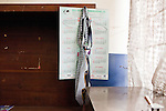 A detective's ties hang, ready to wear, above a bookshelf in his office.