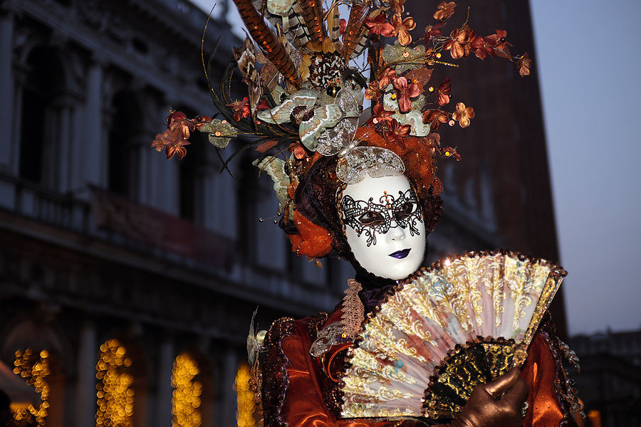 Woman dressed in traditional mask and costume for Venice Carnival standing in Piazza San Marco in front of Saint Mark's Basilica, Venice, Veneto, Italy