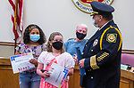 """WINSTED, CT 051121JS06—Angel Mark, 7, left, and Ellen Priest, 7, both second grade students at Oak Street School, were honored as """"little heroes""""  by Police Chief William Fitzgerald during the Board of Education meeting Tuesday at Winsted Town Hall. The two were recognized for alerting another adult that their teacher was suffering from a medical emergency. <br /> Jim Shannon Republican American"""