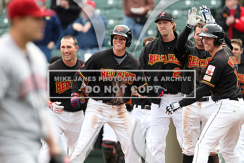 Rochester Red Wings players Brian Dinkelman #12, Chase Lambin #2, Jim Hoey #22, Matt Brown #11, and Dustin Martin #16 celebrate a walk off home run during the first game of a double header against the Lehigh Valley Ironpigs at Frontier Field on April 14, 2011 in Rochester, New York.  Ironpigs pitcher Vance Worley walks off the field in the foreground.  Rochester defeated Lehigh Valley 3-1 with a walk off home run in the bottom of the seventh.  Photo By Mike Janes/Four Seam Images